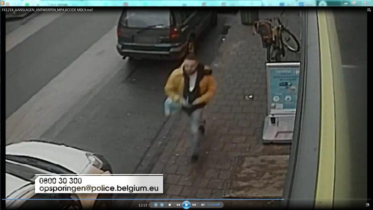 Een verdachte man met mosterdgele jas komt teruggelopen nadat hij een aanslag met twee brandbommen heeft gepleegd in de Lange Lobroeckstraat.