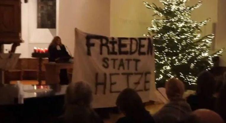 De activisten ontrolden een spandoek met de boodschap 'Vrede in plaats van haat' en scholden de predikante uit.