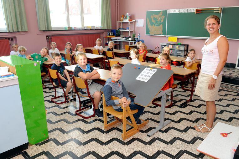 Xander Van Der Meulen met zijn juf en klasgenootjes in de klas. Xander kreeg zelfs een aangepaste lessenaar en stoel.