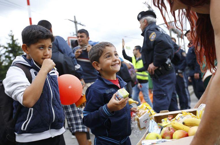 Een vrijwilliger deelt voedsel uit aan vluchtelingenkinderen. Beeld reuters