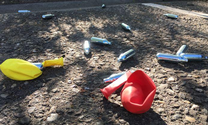 Lege patronen lachgas en ballonnetjes na gebruik achtergelaten op een parkeerplaats.