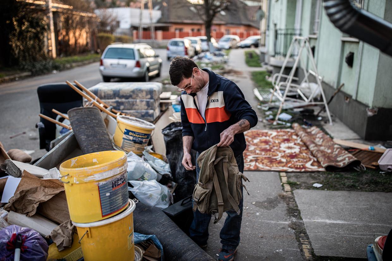 Sandor Jakab kijkt of er nog iets van waarde te vinden is in het tiende disctrict op de jaarlijkse 'ont-afval-dag' in Boedapest.  Beeld Akos Stiller