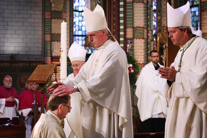 Handoplegging bij Ron van den Hout door Gerard de Korte , geflankeerd door zijn Bossche hulpbisschop Rob Mutsaerts.