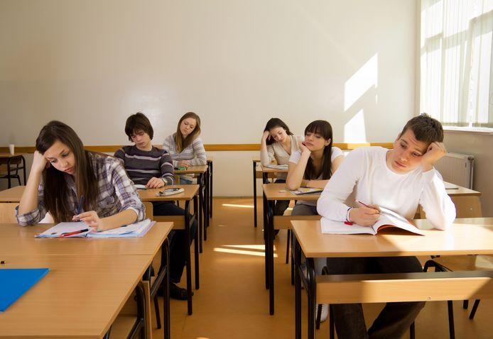 Verveelde scholieren tijdens de les. Illustratiebeeld.