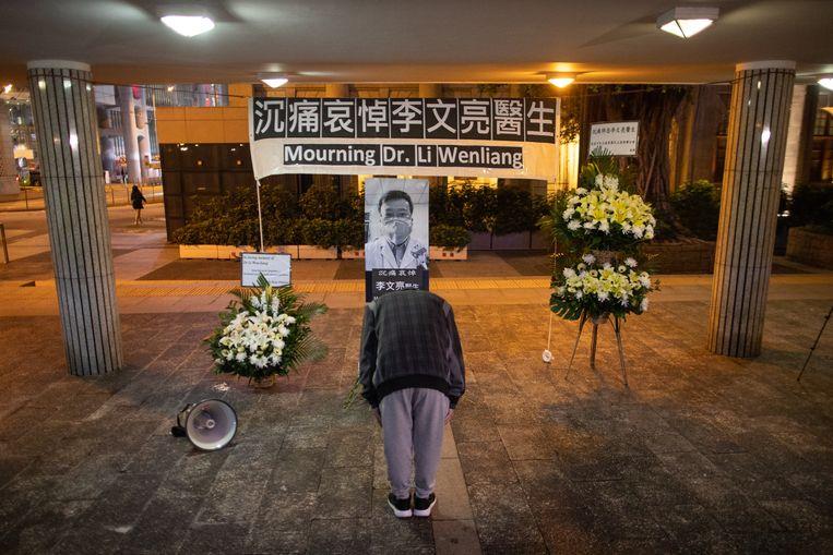 In Hongkong buigt een man voor de foto van de overleden Chinese arts. Op het spandoek de tekst 'In diepe rouw gedenken wij dr. Li Wenliang'. Beeld null