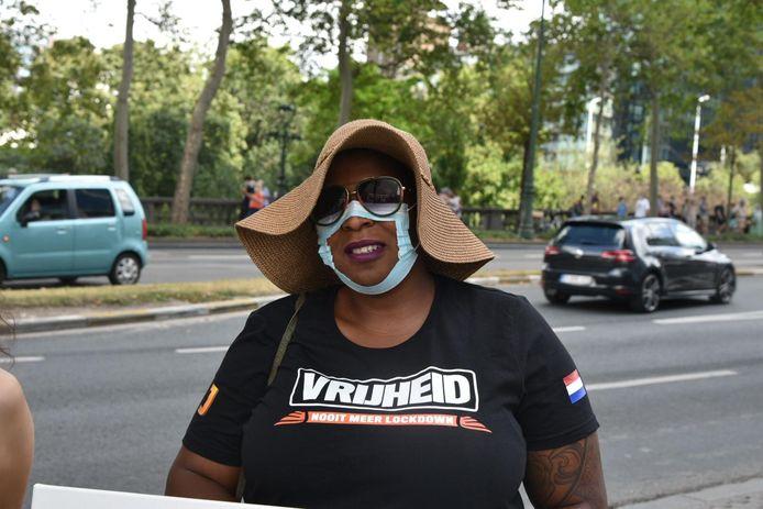 Zelda Schrama knipt een mondmasker stuk uit protest tegen de coronamaatregelen.