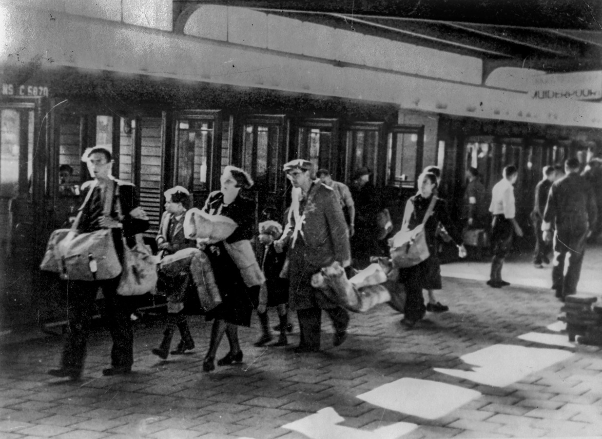 Gezinnen met bagage op een perron. Waarschijnlijk is de foto genomen op het Muiderpoort station in Amsterdam in de zomer van 1943.