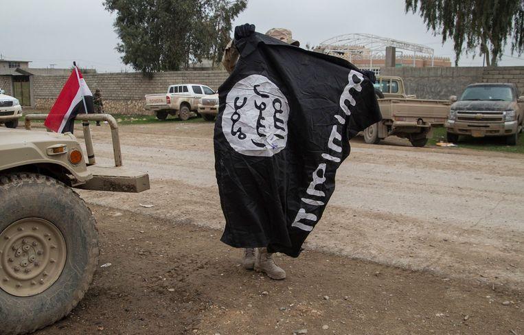 Een lid van het Iraakse leger met een vlag van IS.