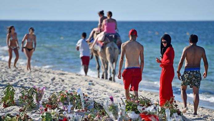 Op het strand liggen bloemen ter nagedachtenis aan de slachtoffers van de bloedige aanslag.