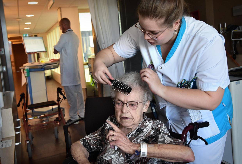 Een arts doet zijn ronde in het ziekenhuis Bernhoven in Uden, terwijl een verpleegkundige de patiënt verzorgt. Beeld Marcel van den Bergh / de Volkskrant