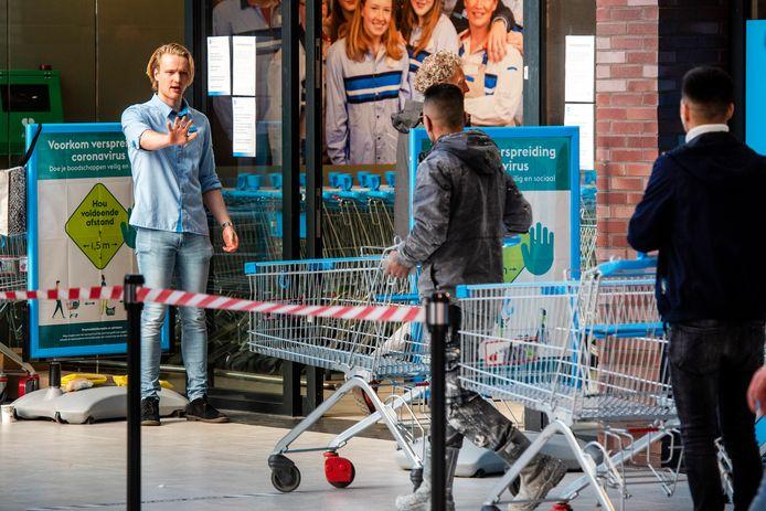 Een supermarktmedewerker regelt het verkeer bij de ingang van de Albert Heijn-vestiging in het Arnhemse winkelcentrum Presikhaaf.