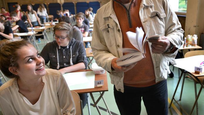 Een docent Nederlands controleert bij het eindexamen een woordenboek op spiekbriefjes