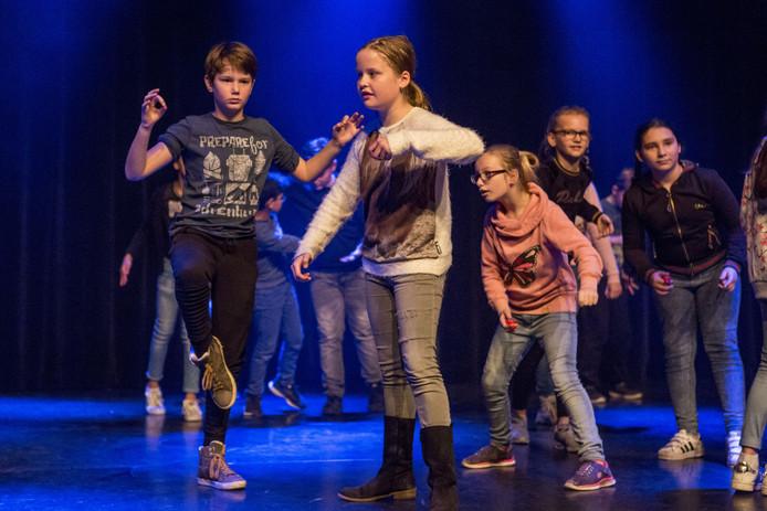 OLDENZAAL - Groep basisschoolleerlingen (Groep 7 van De Maten), die een dans heeft ingestudeerd. Het resultaat wordt opgenomen op het podium van De Bond met rook- en lichteffecten.