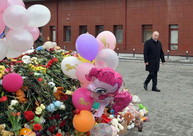 Poetin liet zich niet zien op de plek waar de demonstranten verzameld waren; hij legde een krans bij het afgebrande gebouw, zonder publiek erbij. Beeld AP
