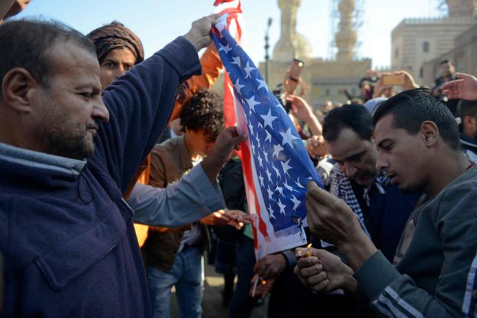Betogers verbranden een Amerikaanse vlag.