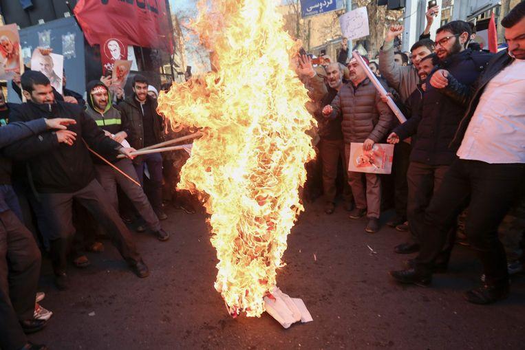 Iraanse betogers verbranden aan de Britse ambassade in Teheran een Britse en Israëlische vlag.