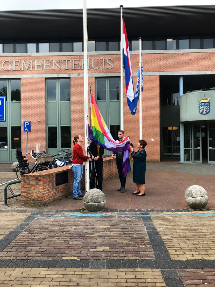 Inge van Beers (links) hijst samen met de Oisterwijkse wethouder Stefanie Vatta (achter de vlag), het Haarense raadslid Boy Scholtze en de Haarense wethouder Adrienne Verschuren de regenboogvlag voor het gemeentehuis in Haaren