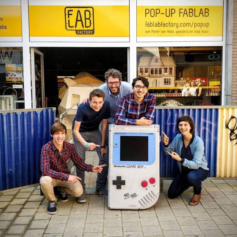 Ilhan Ünal met zijn Game Boy en het FabLab-team in de Pieter Van Aelst-galerij in Aalst.