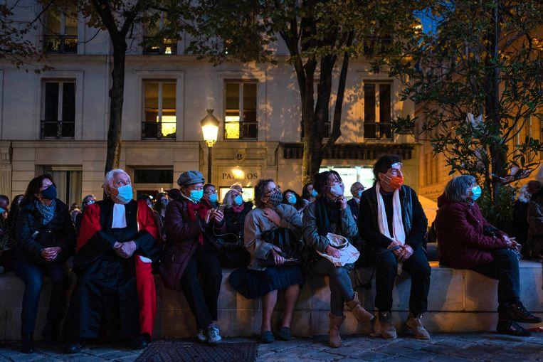 Mensen komen bijeen op Place de la Sorbonne in Parijs om een livestream te volgen van het nationaal eerbetoon aan Samuel Paty. Beeld Getty Images