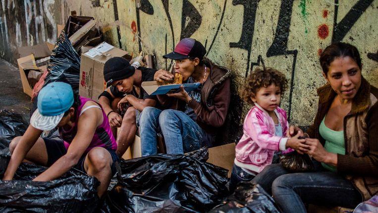 Een familie in Caracas haalt eten uit afvalzakken. Ruim 80 procent van de Venezolanen leeft in armoede. Beeld Meridith Kohut