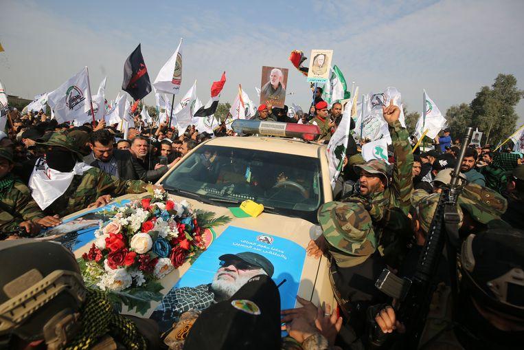 Betogers in Bagdad rondom de auto waarin de kist van Abu Mahdi al-Muhandis wordt vervoerd. Beeld AFP
