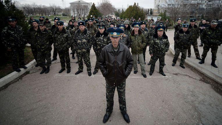 Soldaten van de luchtmacht in Belbek, vlak bij Simferopol, staan tegenover pro-Russische demonstranten vlak buiten hun basis. Beeld afp
