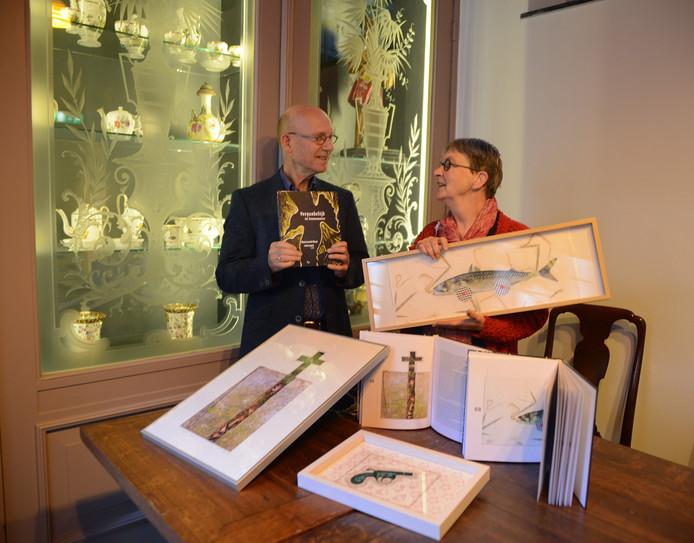 Marco van de Plasse en Saskia Eggink met het boek en enkele van de werken die Eggink maakte voor het boek . Zoals de snoek.
