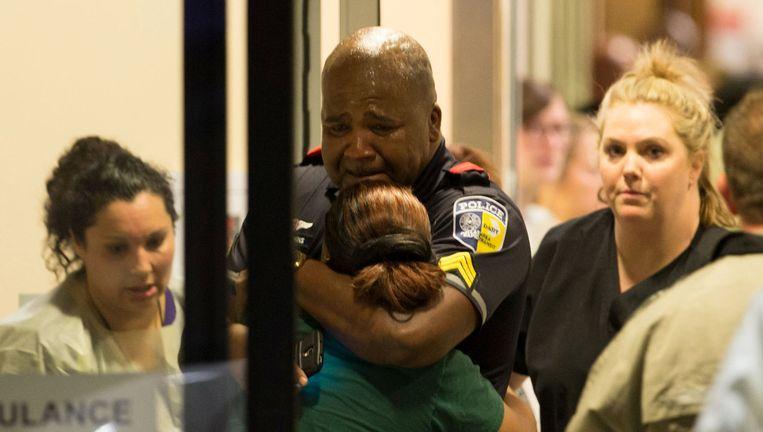 Een politieagent met zijn geliefden bij het ziekenhuis in Dallas na de schietpartij Beeld reuters