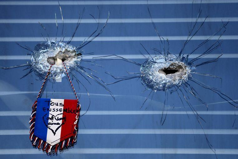 Kogelgaten in het raam van een getroffen restaurant. Beeld ap