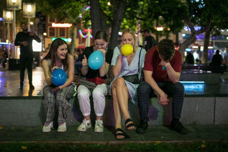 Gebruikers van lachgas op het Rembrandtplein. Beeld Amaury Miller