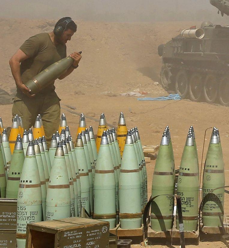 Een Israëlische soldaat draagt een granaat naar een voertuig dat vuurt op doelen in de Gazastrook. Beeld reuters