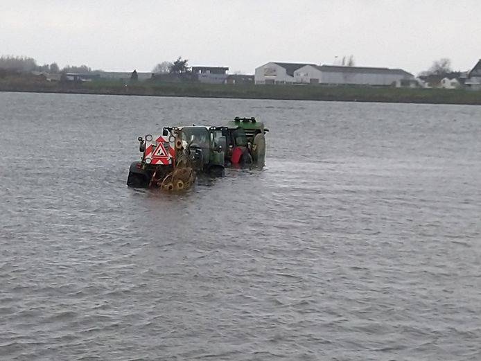 Drie trekkers rijden zich vast in het water van de Boven-Merwede bij Werkendam.