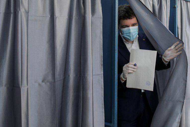 De onafhankelijke kandidaat Nicusor Dan in het stembureau.  Beeld REUTERS