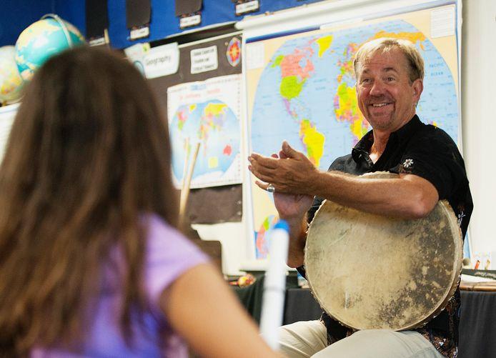 Le professeur de musique John Zeretzke en train d'applaudir ses élèves après une répétition.