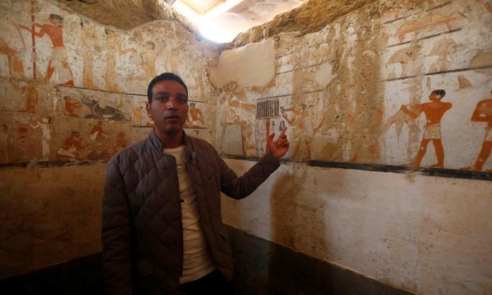 Een gids van het ministerie van Oudheden toont de wandversieringen in het graf van Haptet