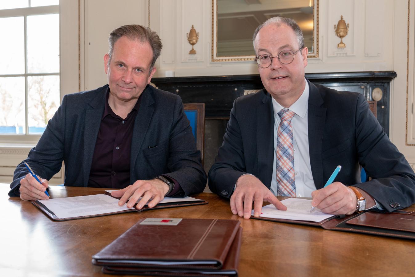 Wethouder Noël Vergunst van Nijmegen (links) en wethouder Johan Sluiter van Lingewaard tekenen de samenwerkingsovereenkomst over de aanleg van de Dorpensingel.