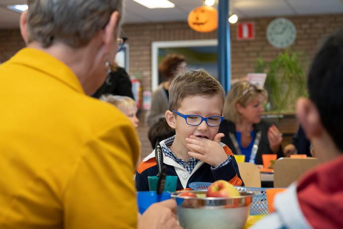 Wethouder Liesbeth Vos met tegenover zich Sjors en op de achtergrond de burgemeester Tanja Haseloop tijdens het schoolontbijt op De Wereldweide vanmorgen.