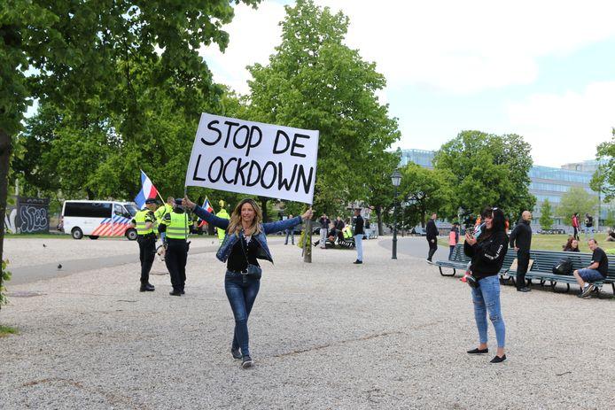 Een vrouw op de Koekamp in Den Haag met een bord waarop valt te lezen: 'Stop de lockdown' bij een eerder protest.