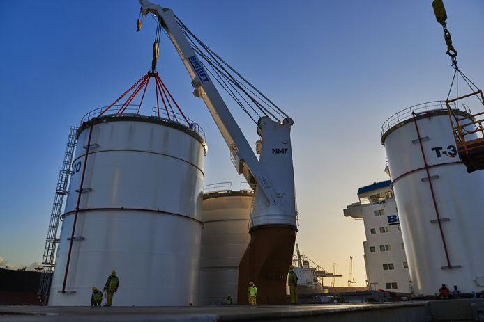 Nieuwe opslagtanks van SJR worden van een schip op hun plek gehesen.