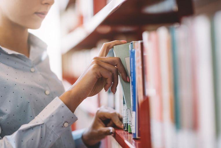Een vrouw pakt een bibliotheekboek uit de kast.