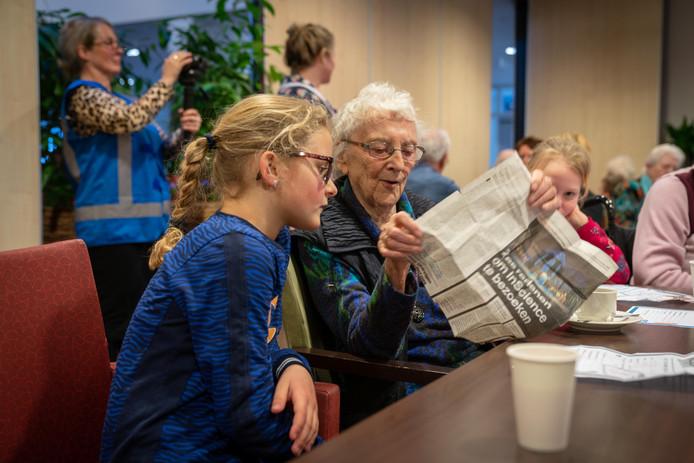 Trees Leenders laat een krantenknipsel zien over de evacuatie in de oorlog. Kinderen van de Vonkenmorgen luisteren geboeid naar de ervaringen van hun, toen nog, leeftijdsgenote.