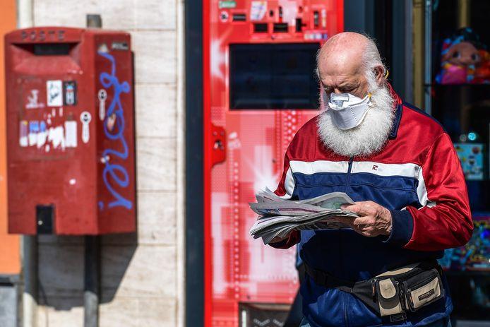 Een inwoner van Bergamo gaat goed beschermd op pad om zijn dagelijkse krant kopen.