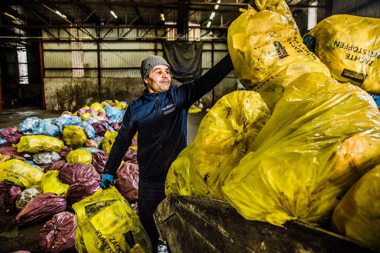 Een vuilnisman scheidt de gele van de blauwe en donkerroze zakken bij een scheidingsstation. Beeld Aurelie Geurts