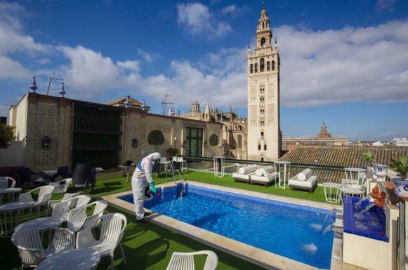 Een medewerker desinfecteert het dakterras van Hotel Dona Maria in Sevilla.