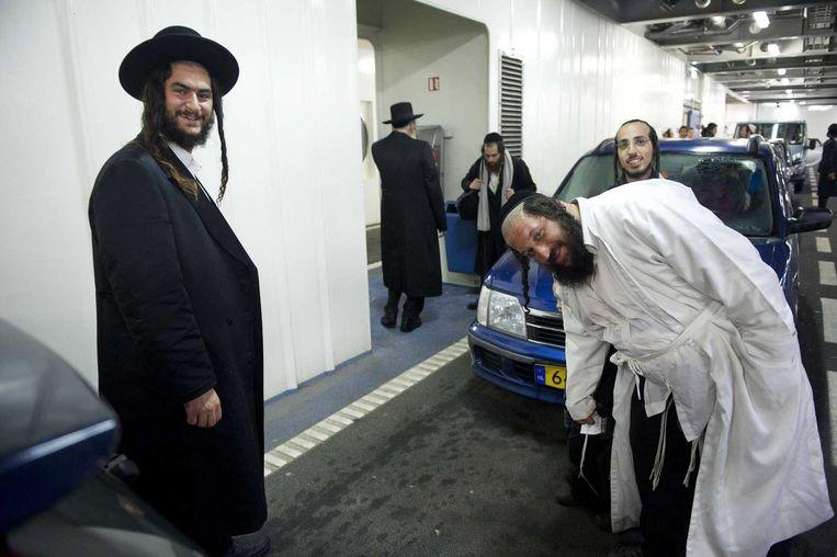 Rabbijn Eliezer Berland wordt afgeschermd door zijn volgelingen en zit met een handdoek over zijn hoofd achterin een auto op de veerboot van Texel naar Den Helder. Beeld anp