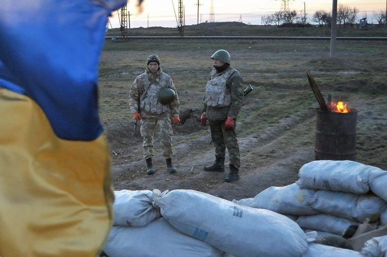 Oekraïense militairen staan op wacht dicht bij de grens met de Krim. Beeld epa