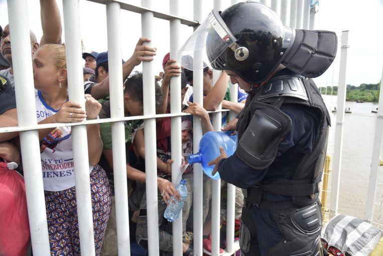 Een Mexicaanse politieagent deelt water uit aan de migranten uit Honduras. Beeld EPA