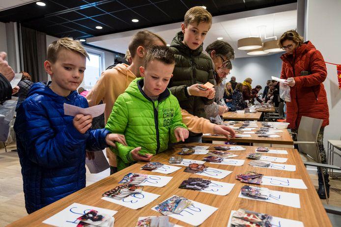 Kinderen zijn naarstig op zoek naar ontbrekende plaatjes voor het stickerboek van sinterklaas.