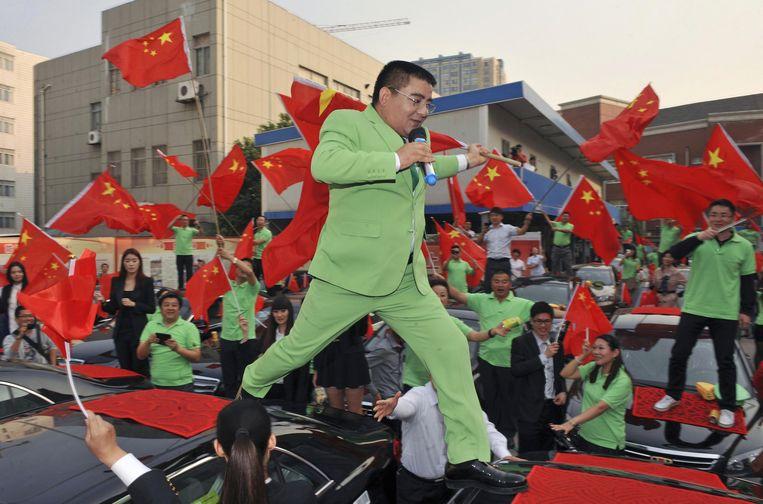 Zingend loopt Chen Guangbiao over auto's die hij doneert aan landgenoten in Nanjing. Hun Japanse auto's waren beschadigd tijdens anti-Japanse protesten. Beeld REUTERS
