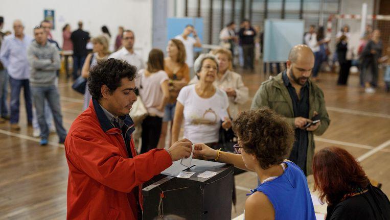 In een gymzaal in Lissabon wordt zondag gestemd. De centrum-rechtse regering lijkt aan de macht te blijven. Beeld getty